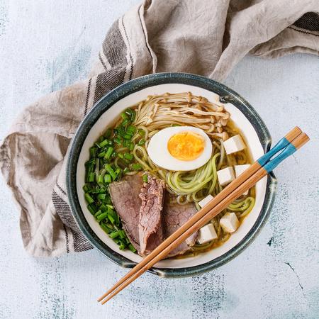 緑茶蕎麦、卵、きのこ、牛肉、ネギ、豆腐チーズ、白い木製の背景に箸と繊維を添えてとアジア風スープのボウル。平面図です。正方形の画像 写真素材