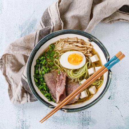 Bowl of asian style soup with green tea soba noodles, egg, mushrooms, beef, spring onion and tofu cheese, served with chopsticks and textile over white wooden background. Top view. Square image