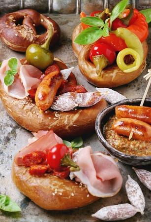 carnes y verduras: Variedad de bocadillos de carne salchichas fritas, wienerwurst, jamón, chiles marinados servido en pretzels salados con albahaca fresca y mostaza sobre fondo de metal viejo. De cerca