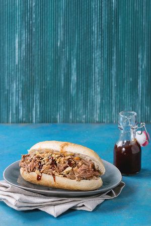 pulled over: Variety of pulled pork sandwiches with meat, fried onion and bbq ketchup, served on gray plate and textile napkin with small bottle of tomato sauce over bright blue wooden background.