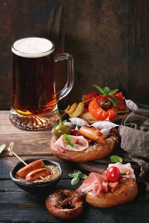 carnes y verduras: Variedad de bocadillos de carne salchichas fritas, wienerwurst, jamón, chiles marinados servido en pretzels salados con albahaca fresca y vaso de cerveza dorada sobre fondo de madera oscura. Foto de archivo