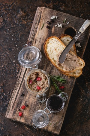 higado de pollo: Glass jars of chicken liver pate with blackcurrant jam, pomegranate grain and sliced bread, served with vintage knife on wooden chopping board over dark texture background. Top view with copy space