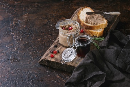 Glass jars of chicken liver pate with blackcurrant jam, pomegranate grain and sliced bread, served with vintage knife on wooden chopping board over dark texture background. Space for text