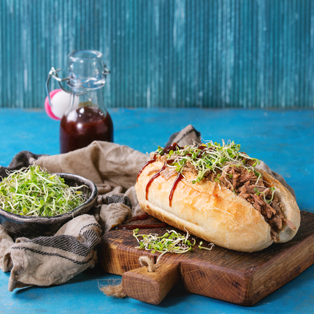 ketchup bottle: Pulled pork sandwich with meat, green sprouts and bbq ketchup, served on wood cutting board with small bottle of tomato sauce and bowl of greens over bright blue wooden background. Square image
