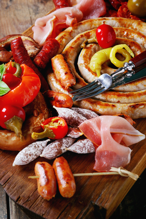 carnes y verduras: Variety of meat snacks fried sausages, wienerwurst, ham, marinated chili peppers served in salted pretzels with cutlery on wood chopping board over dark wooden background. Close up