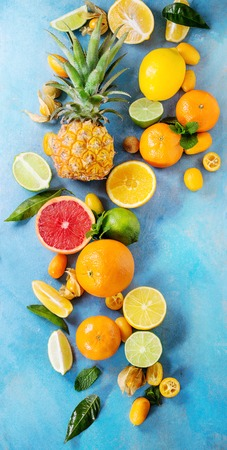 Variety of whole and sliced citrus fruits pineapple, grapefruit, lemon, lime, kumquat, clementine and physalis with mint over blue wooden background. Top view with space. Healthy eating, dieting