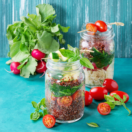 red quinoa: Salads with quinoa, couscous, spinach, radish, tomatoes and zucchini in glass mason jars, standing with fresh vegetables over bright turquoise wooden background. Healthy lunch concept. Square image