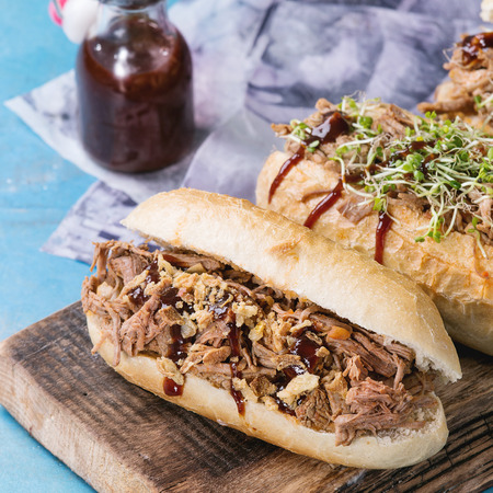 pulled over: Variety of pulled pork sandwiches with meat, fried onion, green sprouts and bbq ketchup, served on wood cutting board with small bottle of tomato sauce over bright blue wooden background. Square image