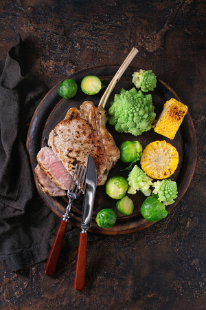 romanesco: Sliced grilled veal tomahawk steak with vegetables brussels sprouts, romanesco and corn cobs served with cutlery on wooden serving chopping board over old wood background. Top view with space. Stock Photo