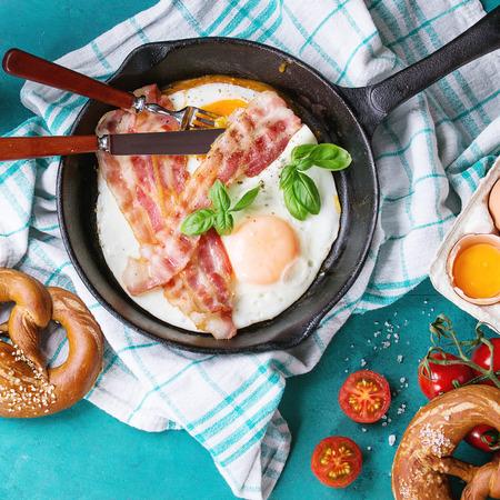 目玉焼きと青緑色の木製の背景に白いキッチン タオルの上に卵、トマト、プレッツェル、バジルが壊れて鋳鉄のフライパンでベーコンの朝食します 写真素材
