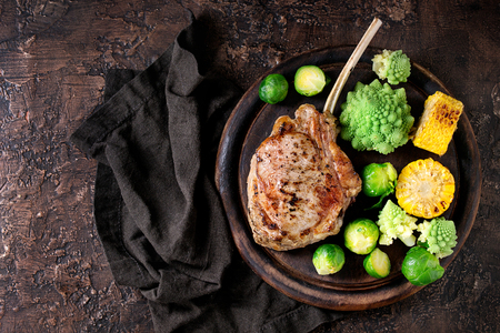 romanesco: Grilled veal tomahawk steak with vegetables brussels sprouts, romanesco and corn cobs served on wooden serving chopping board over old wood background. Top view with space. Ready-to-eat