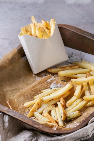 lunch tray: Fast food french fries potatoes with skin served with salt in lunch box on baking paper in old rusty oven tray with kitchen towel over gray texture background. Space for text Stock Photo