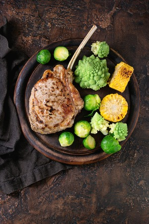 Grilled veal tomahawk steak with vegetables brussels sprouts, romanesco and corn cobs served on wooden serving chopping board over old wood background. Top view with space. Ready-to-eat