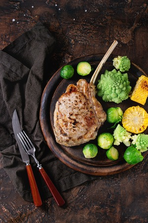 romanesco: Grilled veal tomahawk steak with vegetables brussels sprouts, romanesco and corn cobs served with cutlery on wooden serving chopping board over old wood background. Top view with space. Stock Photo