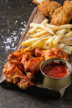 Fast food fried crispy and spicy chicken legs, wings and french fries potatoes with salt and ketchup sauce served on wooden serving board over dark texture background. Space for text