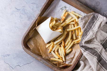 lunch tray: Fast food french fries potatoes with skin served with salt in lunch box on baking paper in old rusty oven tray with kitchen towel over gray texture background. Top view, space for text