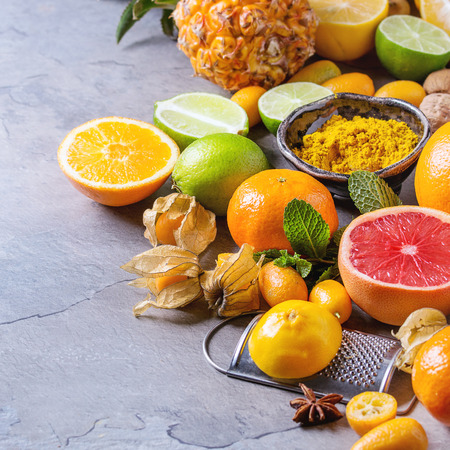 Variety of whole and sliced citrus fruits pineapple, grapefruit, lemon, lime, kumquat, clementine and physalis with mint and yellow spices and nuts over gray textured background. Copy space. Square image