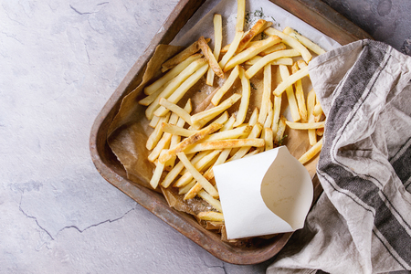 lunch tray: Fast food french fries potatoes with skin served with salt and empty lunch box on baking paper in old rusty oven tray with kitchen towel over gray texture background. Top view, space for text