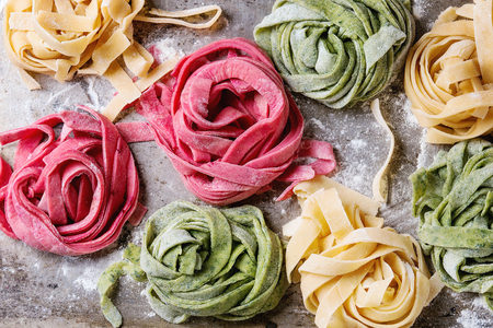 Variety of colored fresh raw uncooked homemade pasta tagliatelle green spinach, pink beetroot and yellow with flour over old metal texture background. Top view. Food background