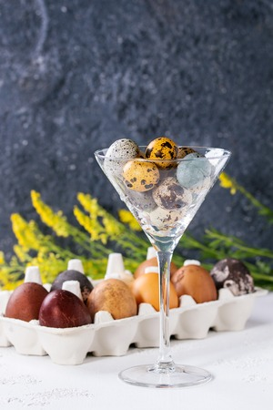 Brown and gray colored chicken and quail Easter eggs in paper box and cocktail glass with yellow flowers bouquet over white and gray concrete texture background. Copy space