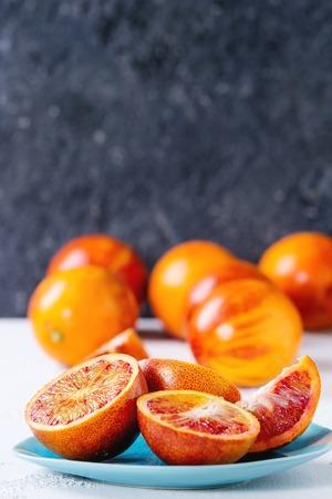 Frutas de naranjas de sangre siciliana jugosas maduras rebanadas y enteras en la placa de cerámica sobre fondo blanco y gris concreto de la textura. Copia espacio Foto de archivo - 71722937