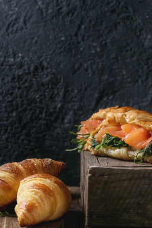 Croissant with smoked salted salmon, spinach and arugula served over dark old wooden table. Copy space