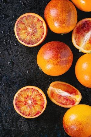 Gesneden en hele rijpe sappige Siciliaanse bloedsinaasappelen fruit op zwarte natte metalen textuur achtergrond. Bovenaanzicht met ruimte