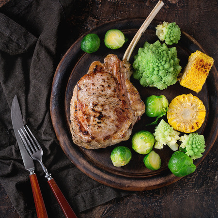 romanesco: Grilled veal tomahawk steak with vegetables brussels sprouts, romanesco and corn cobs served with cutlery on wooden serving chopping board over old wood background. Top view. Square image