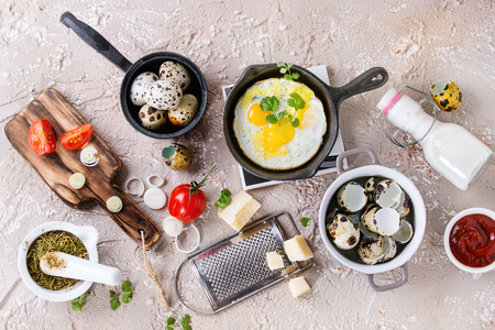 Breakfast with fried quail eggs in iron cast pan, cherry tomatoes, onion, ketchup sauce, seasonings in mortar, cheese grater, egg shell in pot. Beige concrete texture background. Top view with space. Stock Photo