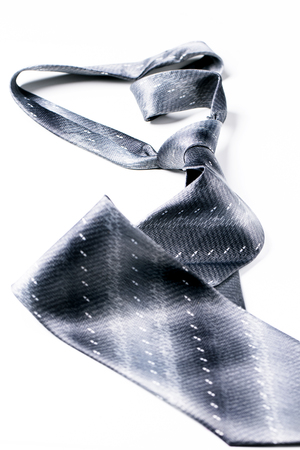 Gray spotted mans knotted tie over white. Isolate.