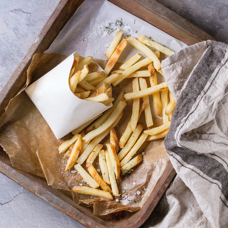 lunch tray: Fast food french fries potatoes with skin served with salt in lunch box on baking paper in old rusty oven tray with kitchen towel over gray texture background. Top view. Square image