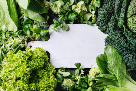 Variety of raw green vegetables salads, lettuce, bok choy, corn, broccoli, savoy cabbage as frame round empty white chopping board. Food background. Top view, space for text Stockfoto
