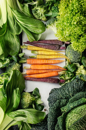 bok choy: Variety of raw green vegetables salads, lettuce, bok choy, corn, broccoli, savoy cabbage, colorful young carrots on white chopping board. Food background. Top view Stock Photo