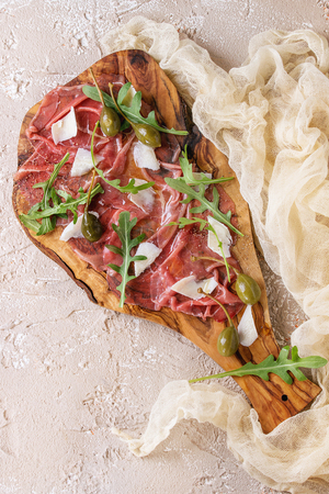 caper: Beef carpaccio on olive wood serving board with capers, olive oil cheese and arugula, served with gauze textile over beige concrete texture background.