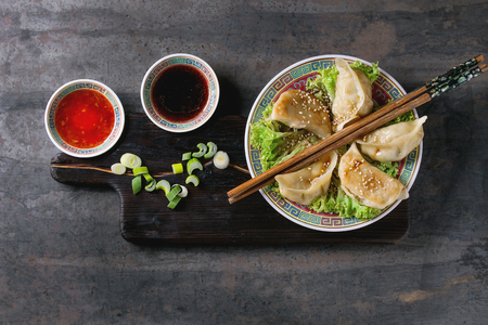 potstickers: Gyozas potstickers on lettuce salad with sauces. Served in traditional china plate with chopsticks and spring onion on wood serving board over old metal background.