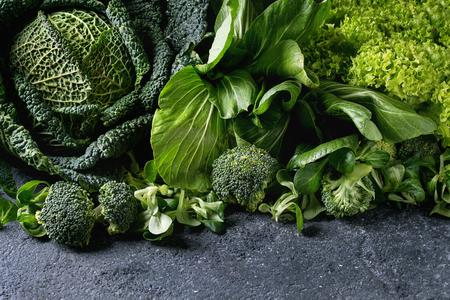 Variedad de ensaladas de verduras verdes crudas, lechuga, col china, maíz, brócoli, repollo de col rizada como marco sobre fondo negro de la textura de piedra. Espacio para texto Foto de archivo