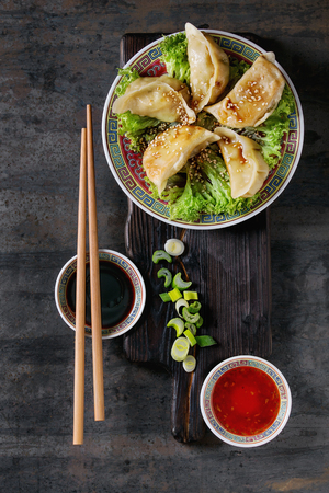 potstickers: Gyozas potstickers on lettuce salad with sauces. Served in traditional china plate with chopsticks and spring onion on wood serving board over old metal background. Top view, space. Asian dinner