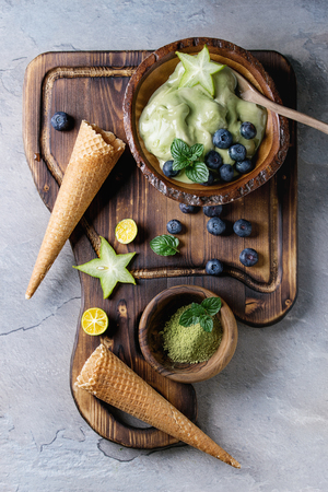 Bowl of Green tea matcha soft elastic ice cream with mint leaves, carambola, lime, blueberries and waffle cones on wooden serving board with wood spoon over gray texture background.