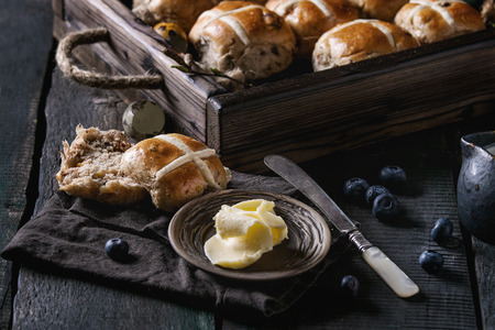 Hot cross buns in wooden tray served with butter, knife, blueberries, easter eggs, birch branch, jug of cream on textile papkin over old texture wood background. Dark rustic style. Easter baking.