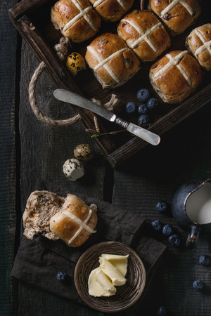 Hot cross buns in wooden tray served with butter, knife, blueberries, easter eggs, birch branch, jug of cream on textile papkin over old texture wood background. Top view, space. Easter baking.