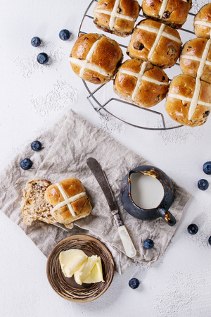 Hot cross buns on baking rack served with butter, fresh blueberries, knife and jug of cream on textile napkin over white texture concrete background. Top view, space. Easter baking.