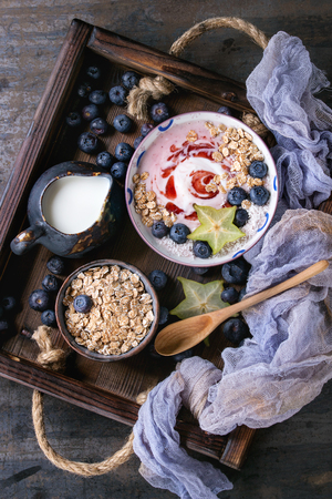 Smoothie bowl healthy breakfast. Strawberry yogurt with blueberries, granola, mint, jug of milk and carambola in wooden tray on textile gauze over dark metal texture background. Top view Stock Photo