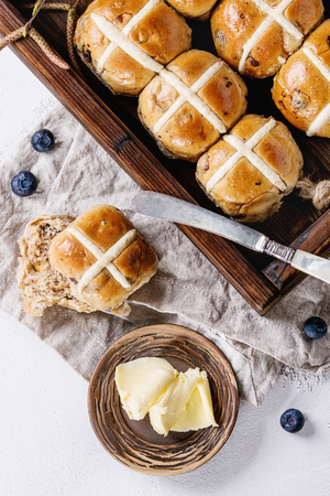 Hot cross buns in wooden tray served with butter, fresh blueberries, knife and jug of cream on textile napkin over white texture concrete background. Top view, space. Easter baking. Stock Photo