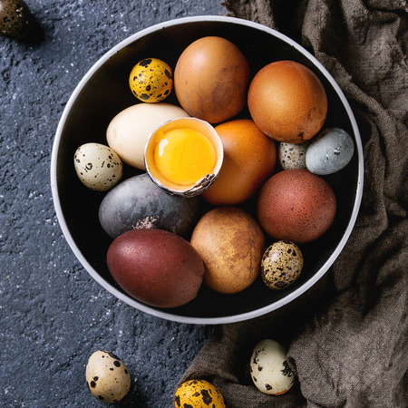 Brown and gray colored chicken and quail Easter eggs in black ceramic bowl with yolk, sackcloth rag over black concrete texture background. Top view, space. Square image Stock Photo