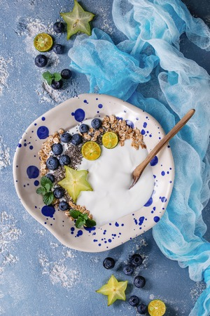Smoothie bowl healthy breakfast. Yogurt with blueberries, granola, chia seeds, lime, wooden spoon, mint and carambola on textile gauze over blue concrete texture background. Top view, space Stock Photo