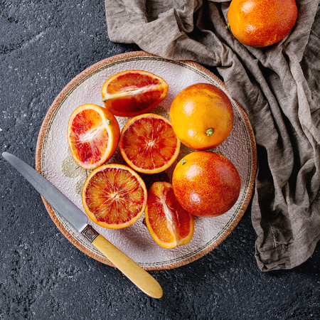 Sliced and whole ripe juicy Sicilian Blood oranges fruits with knife, sackcloth rag on ceramic plate over black concrete texture background. Top view. Square image
