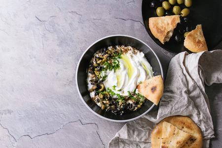 Labneh Nahöstlichen libanesischen Frischkäse Dip mit Olivenöl, Salz, Kräuter, Oliven-Tapenade serviert in schwarzer Schale mit traditionellen Pitabrot über graue Textur Metall Hintergrund. Draufsicht mit Platz Standard-Bild - 74825651