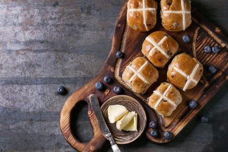 Hot cross buns on wooden cutting board served with butter, knife, fresh blueberries and jug of cream over old texture metal background. Top view, space. Easter baking. Stock Photo