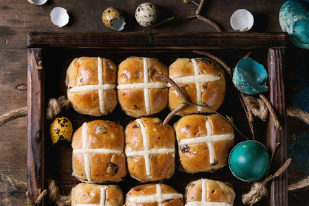 Hot cross buns in wooden tray served with butter, knife, blueberries, easter eggs, birch branch over old wood background. Top view. Easter baking.
