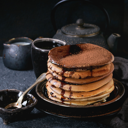 Stack of homemade american ombre chocolate pancakes with carob honey sauce and cocoa powder served on black plate with jug of cream and teapot over black stone texture background. Square image